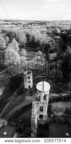 Blarney, Ireland. Autumn in Ireland. Aerial view of Blarney Castle tower in Ireland. Forest and fields at the background. Black and white