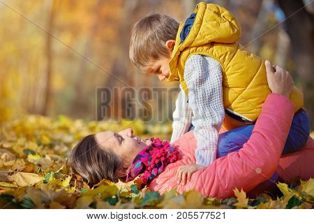 Happy beautiful mother with her little son playing in the park
