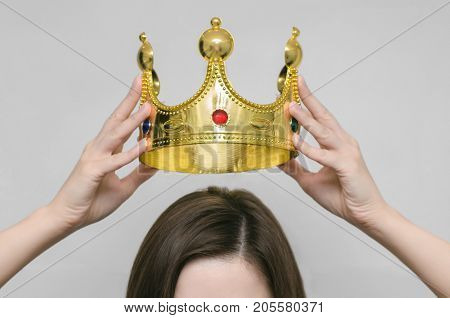 Woman girl holding above a head the golden crown. Leadership success queen.