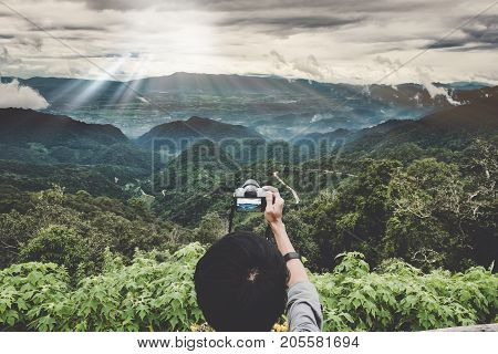 Enjoy Travel With Peak Of Mountaon. A Backpacker Hand Holding A Digital Camera At Peak Of Mountain T