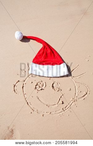 drawing of a happy face with a smile and a red cap of santa on the sand of the red sea
