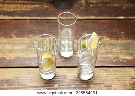 empty shot glasses for a cocktail shot with a slice of lemon on a wooden background