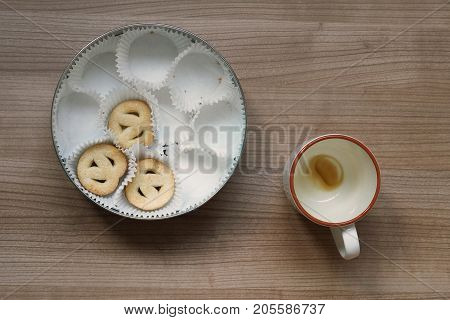 topview of empty coffee cup and cookie tin on table