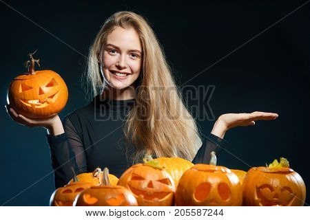 Happy smiling woman with Halloween pumpkins over dark background showing open hand palm with copy space
