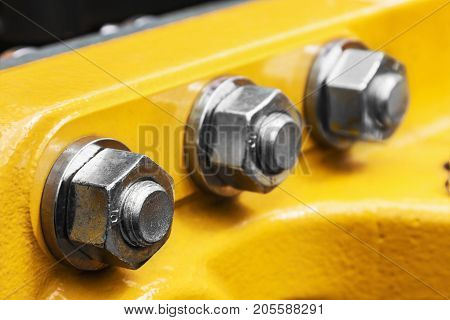 bolt and nut spun on the tractor or other construction equipment. focus on the nut of the foreground