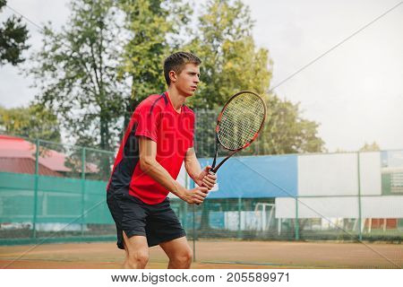 Handsome man in shirt holding tennis racket and looking concentrated while standing on tennis court. Outdoot. Copy-space
