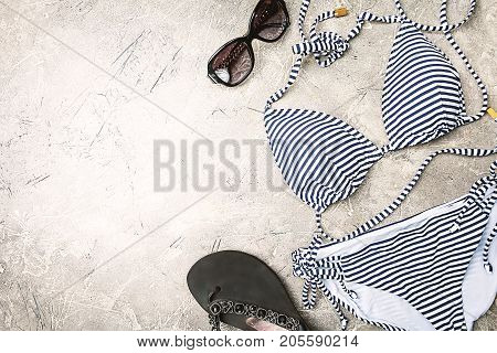 Female summer striped bikini swimsuit, clothes and accessories collection on gray background. Flat lay, top view