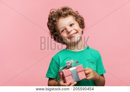 Little curly boy in casual t-shirt holding small giftbox and smiling away on pink background.