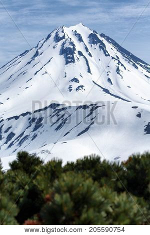 Volcanic landscape of Kamchatka Peninsula: view of snow-capped cone of Vilyuchinsky Volcano at sunny day. Photo stratovolcano photographed with Vilyuchinsky Pass. Russian Far East Kamchatka Region.