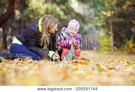 Little girl and mother playing with toy dinosaur in autumn park