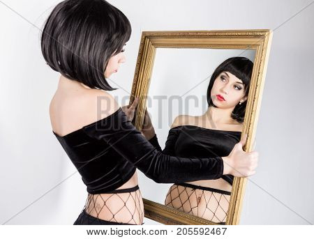strange brunette woman make faces and looking on herself in mirror. poster