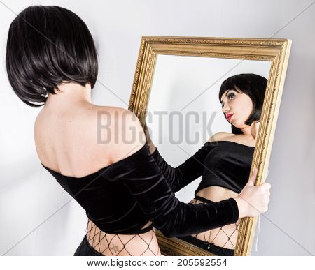 strange brunette woman make faces and looking on herself in mirror.