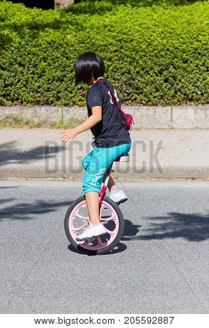 OSAKA JAPAN - SEPTEMBER 18 : unidentified asian little girl riding a unicycle (one wheel bike) in a park on September 18 2017 in Osaka Japan.
