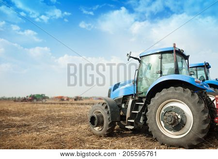Two blue tractors in the empty field. Agricultural machinery