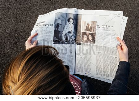 PARIS; FRANCE - SEP 24; 2017: View from above of woman reading latest newspaper Le Monde with portrait of Liliane Bettencourt. Liliane Henriette Charlotte Bettencourt was a French heiress socialite and businesswoman. She was one of the principal sharehold