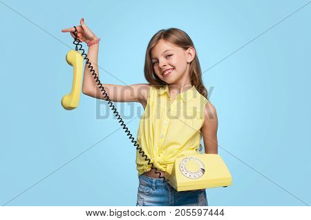 Little adorable girl holding obsolete telephone smiling at camera on blue background.