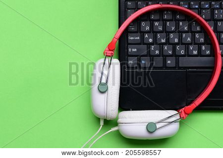 Earphones With Computer On Light Green Background. Sound Recording Idea
