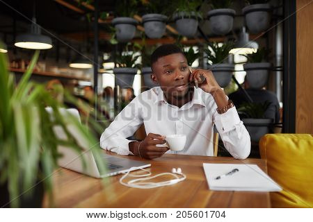Young african businessman discussing, talking at call phone and drinking coffee in cafe at break. Angry male studding at restaurant, decided problem. Freelancer working with laptop in restaurant.