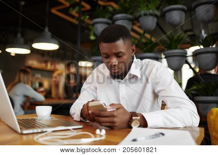 View of serious african man typing, chatting, working in stylish cafe. Handsome freelancer using smart phone, writing message. Student learning at freelance. Coffee break. Loft interior of restaurant.
