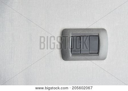 Dark grey light switch with wall texture background. Copy space.