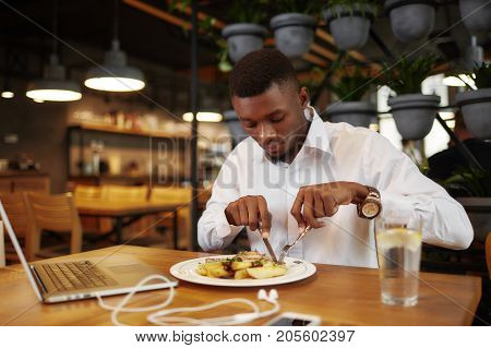 View of young handsome african man have dinner at cafe, when having break, after work with laptop. Freelancer male, or businessman using call phone and gadget for work, resting and eating tasty dish.