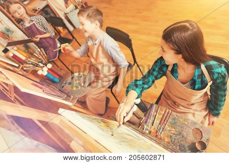 Fun and educative activity. Creative youngster laughing and joking while sitting at their easels and having a painting class all together.