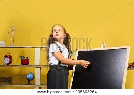 Childhood and study time concept. Schoolgirl with dreamy face and ponytails stands in her classroom. Kid and school supplies on yellow wall background. Girl writes on blank blackboard copy space