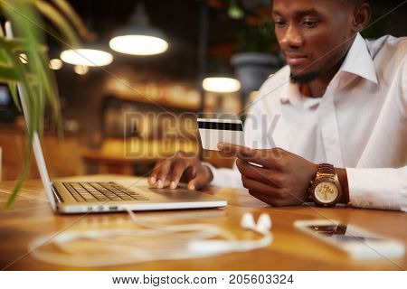 African man in white shirt holding plastic credit card, typing, using laptop, doing order from internet. Serious businessman sending money or paying with card. Shopping. Working in cafe.