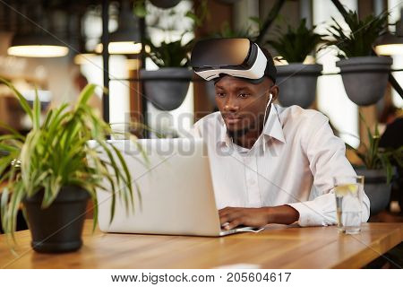 View of young african man wearing in head set of virtual reality, using, looking at screen of laptop. Handsome male in white shirt, working with gadget, listening music, sitting at cafe. Technology of future.
