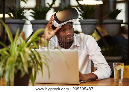 Young african man with glasses of virtual reality on head, using, working at laptop, turned, looking away. Handsome male in white shirt, working at cafe, listening music. Imitation of reality.