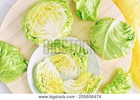 fresh green cut head of cabbage on ceramic gray plate, wooden and material background