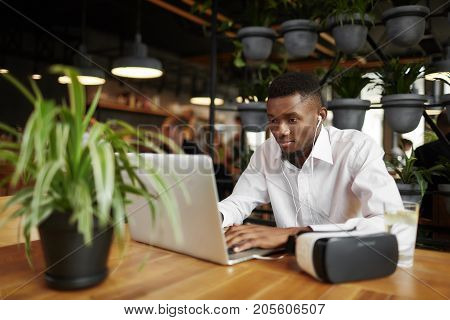 African man in white shirt typing at laptop, using, looking at screen. Handsome male working with gadget, listening music, sitting at cafe. Near head set of virtual reality.