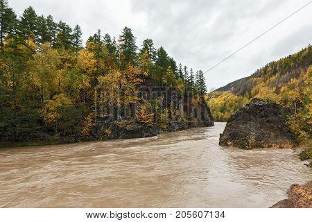 Beautiful Kamchatka autumn landscape: mountain river flowing among roky mountain through the colorful forest. Eurasia Russian Far East Kamchatka Peninsula.