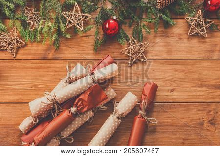 Christmas decoration, gift boxes candies in craft paper with twine and garland frame background, top view on wood surface. Christmas ornaments and presents border with balls and stars, copy space