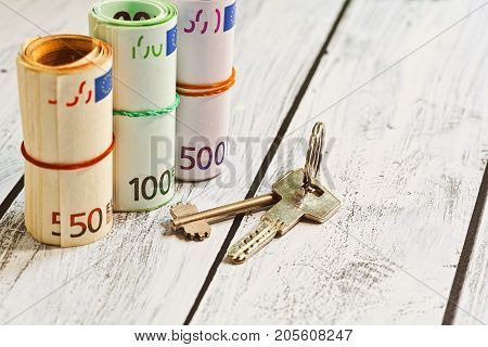 A large sum in cash - european union currency money - and a bunch of door lock keys on the wooden table. Purchasing or selling estate property concept or long-term rent deposit.