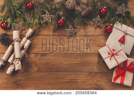Christmas decoration, gifts candies and boxes in craft paper with twine and garland frame background, top view on wood surface. Christmas ornaments and presents border with balls and stars, copy space