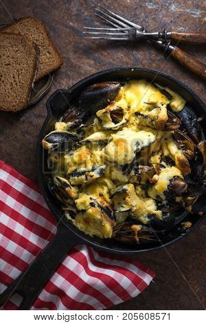 Mussels with cheese sauce in a frying pan, napkin in a red cage vertical