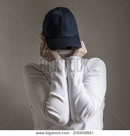 Lady hiding her face behind a hat