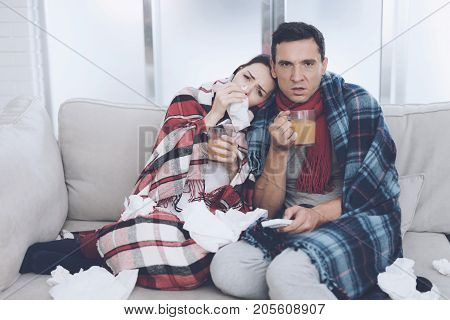 The couple is sitting on the couch wrapped in blankets. Man and woman are sick. A man and a woman are sitting on the couch and drinking therapeutic tea from glass cups