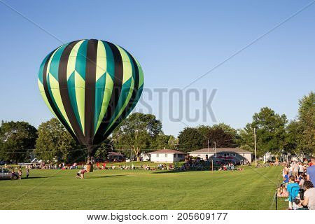 Seymour WI - August 12 2017: Hot air balloon being sent aloft during Hamburger Fest in Seymour WI. Hot air balloons are an integral part of the annual festival which celebrates Seymour as the birthplace of the hamburger.