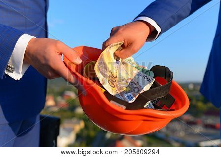 corruption.Bribery and business bargain concept. Businessmens hands with money on outside background. Male hands put stack of dollar bills into orange helmet. Money in different banknotes in close up