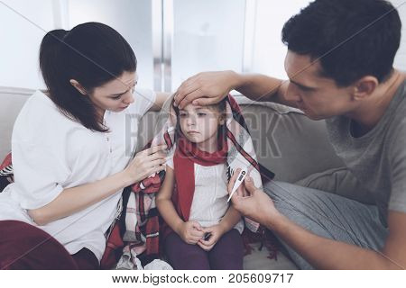 The little girl caught a cold. Her mother and father are treating her. Father measures the girl's temperature. The mother sits next to her and worries about it.