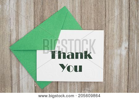 Thank You message An embossed white card with green envelope on weathered wood with text Thank You