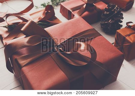 Christmas eve, preapring for holidays. Gift wrapping. Packaging stylish present boxes in maroon paper decorated with satin ribbon bows. Winter holidays concept, closeup