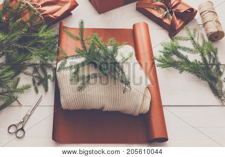 Gift wrapping background. Sweater as christmas present in maroon paper decorated with satin ribbon. Winter holidays concept. Top view of white wood table with fir tree branches
