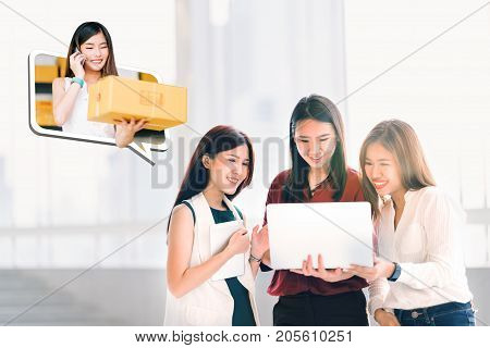 Young Asian women or coworkers using laptop computer shopping online together. Business owner girl confirm purchase order sending product package delivery. E-commerce e-payment or startup concept.