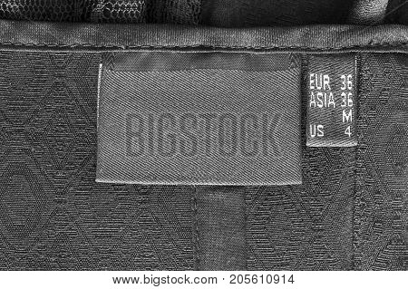 Black blank clothes label on black textile background closeup