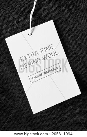 Lettered clothes label on black wool background closeup