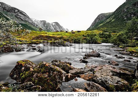 Wide panoramic long exposure of grass roof houses in the mountains of Norway with green meadows and a white water river in the foreground