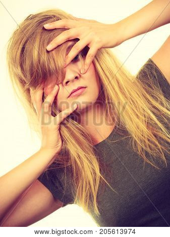 Emotions embarrassment awkwardness gestures concept. Ashamed blonde woman covering her face with hands. Studio shot on white background.